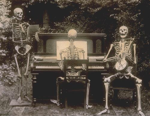 three skeletons at a piano